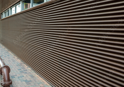 Building exterior wall facade with horizontal lines for texture with windows at top and adjacent sidewalk Canvas Print