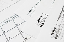 IRS Form 1095-A 1095-B And 1095-C Blank Lies On Empty Calendar Page