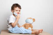 Teaching Your Child Preventive Measures Against Viruses And Flu. Baby, Boy In A Medical Mask Puts A Medical Mask On His Teddy Bear Toy. Care For Loved Ones. Basic Hygiene Rules