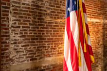 American Flag On Stand, Against Old Brick Wall, With Copy Space.