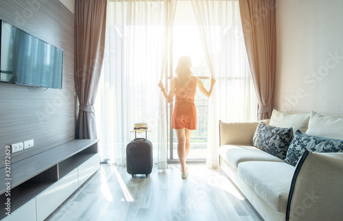 Fotografie, Obraz Portrait of tourist woman standing nearly window, looking to beautiful view with her luggage in hotel living room after check-in