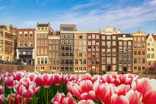 Obraz na plátně Amsterdam Netherlands, city skyline at canal waterfront and bridge with spring t