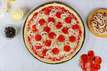 Raw Uncooked Pizza With Pepperoni And Mushroom.