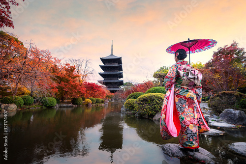 Tablou Canvas Young Japanese girl traveller in traditional kimino dress standing in Toji temple with wooden pagoda and red maple leaf in autumn season in Kyoto, Japan