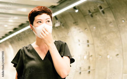 Fototapeta Beautiful middle aged Asian woman stand alone, look worried, cover mouth, wear medical face mask to protect from infection of virus, pandemic, influenza outbreak and epidemic of disease in city mall. obraz