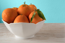Fresh Oranges In White Porcelain Bowl. Healthy Citrus Fruits On Blue Background. Kitchen Concept