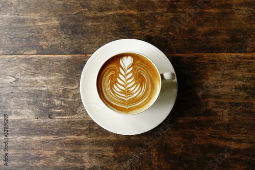 a cup of latte art coffee on wooden background Canvas Print