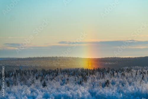 Photo Snowy winter rainbow at  (halo) dawn in the polar Russia.