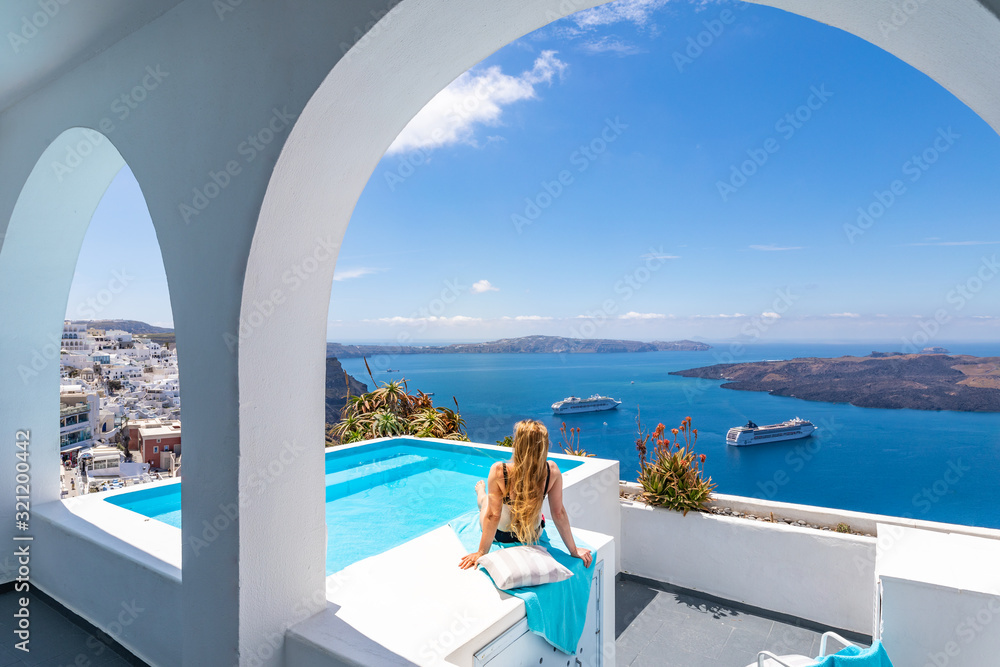 Fototapeta Luxury summer vacation background. Young woman on vacation at Santorini, women at the swimming pool looking out over the Caldera ocean of Santorini, Girl at the infinity pool Santorini Greece