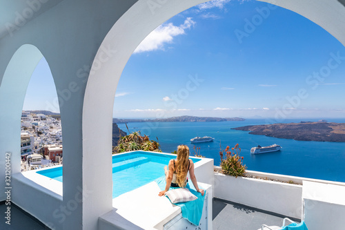 Fototapeta Luxury summer vacation background. Young woman on vacation at Santorini, women at the swimming pool looking out over the Caldera ocean of Santorini, Girl at the infinity pool Santorini Greece obraz