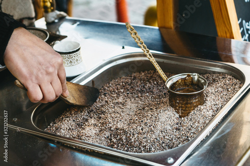 Photo Making traditional black Turkish coffee or espresso in the sand in a special Turk