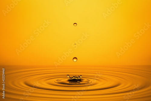 Fototapety, obrazy: Golden Oil Drops on Yellow Background.