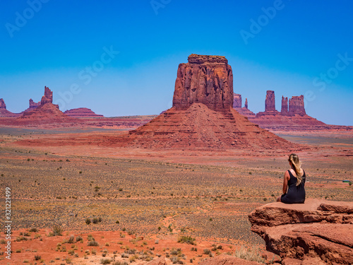 Young blonde girl admires panorama from Artist's Point in Oljato Monument Valley, region of Colorado Plateau characterized by cluster of vast sandstone buttes, Arizona Utah border Wallpaper Mural