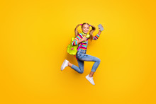 Full Body Profile Side Photo Kid Jump Run Fast Lesson Schoolgirl Hold Smartphone Headset Striped Sweater Denim Jeans Rucksack Bag Suspenders Overalls Isolated Bright Shine Yellow Color Background