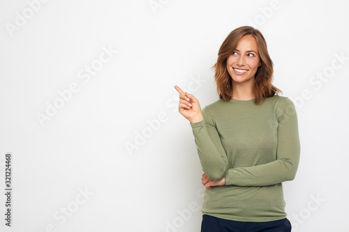 Obraz young woman pointing at your product and looks at it. - fototapety do salonu