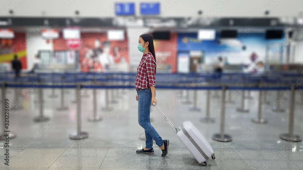 Fototapeta Asian tourist with luggage ,wearing mask to prevent during travel time at the airport terminal for protect from the new Coronavirus 2019 infection outbreak situation