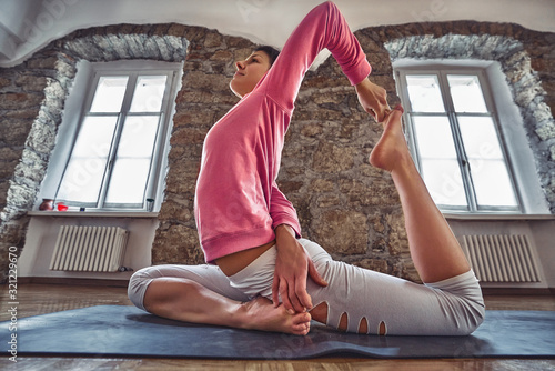 Young woman exercise yoga on a mat in the loft interior Wallpaper Mural