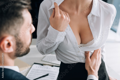 Obraz cropped view of businessman hugging sexy secretary with big breast in office - fototapety do salonu