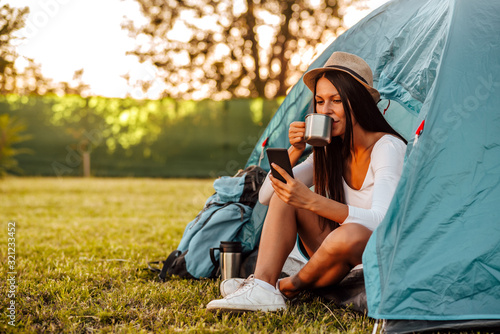 Fototapeta Portrait of a young woman at camping, sitting at tent drinking coffee and looking at smart phone. obraz