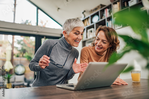 Fototapeta Senior mother and adult daughter relaxing and looking at laptop together, at home, portrait. obraz