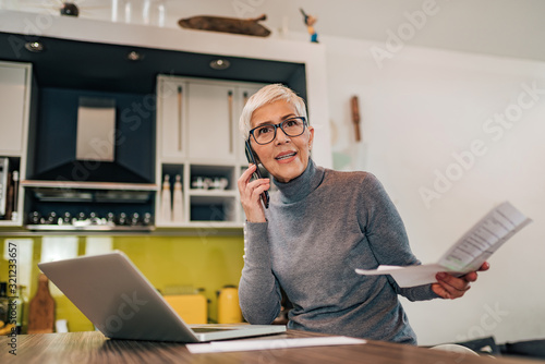 Portrait of a mature woman arguing over mobile phone and holding document while sitting in front of laptop in the kitchen Canvas Print