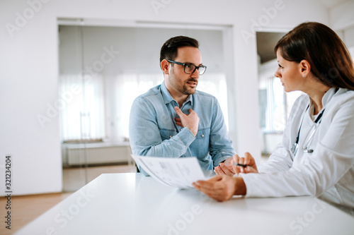Handsome male patient talking to a female doctor, portrait. Poster Mural XXL