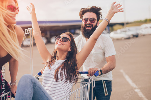 Cheerful hipster pushing shopping trolley with friends