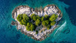 Aerial view of the heart shaped island . Blue ocean sea with wave and small forest and rocky coastline.