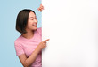 Cheerful Asian woman pointing at blank poster