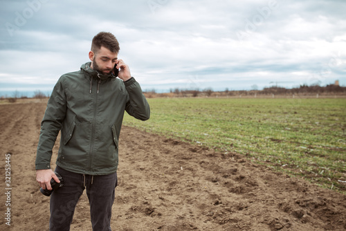 Photo Young farmer working in a wheat field, talking mobile phone