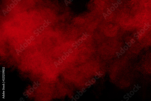 Fototapety, obrazy: Red color powder explosion on black background.Freeze motion of red dust particles splashing.