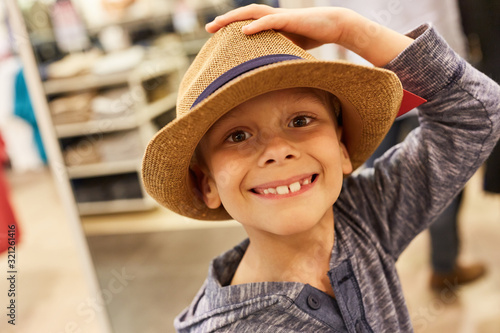 Happy boy at the hat shop Canvas Print