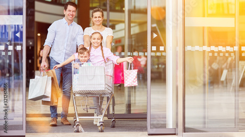 Family with children in shopping cart while shopping