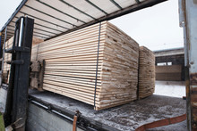 Wood Transportation. Forklift Loading Truck With Freshly Cut Wooden Planks For Construction Industry.