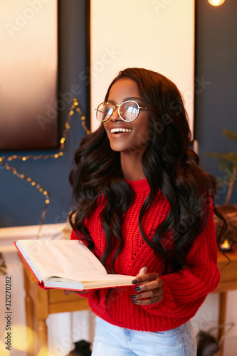 Black girl in a beautiful, knitted red sweater and a book in her hands laughs standing in the home interior Fototapeta