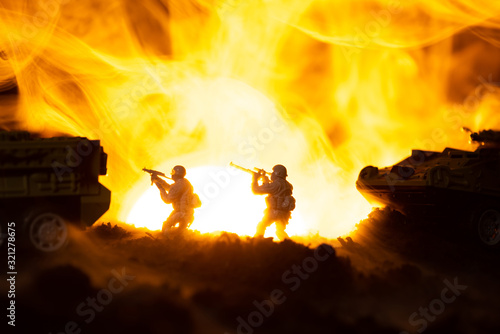 Fototapeta Silhouettes of toy warriors with tanks in fire and sunset at background, battle scene obraz