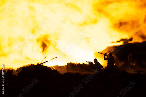 Fototapeta Battle scene with toy soldiers and tank on battleground with fire at background obraz