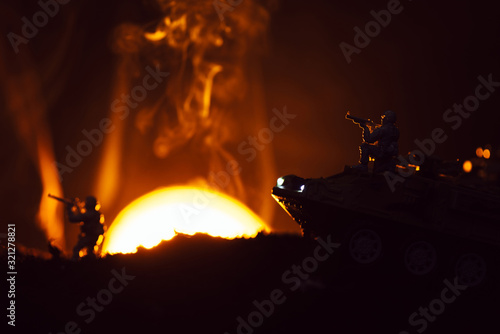 Fototapeta Battle scene with toy warriors and tank in smoke with sunset at background obraz