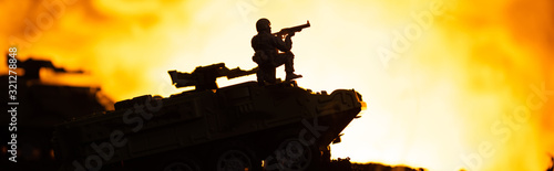 Fototapeta Battle scene with silhouette of toy soldier on tank with fire at background, panoramic shot obraz