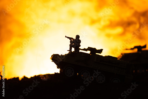 Fototapeta Silhouette of toy soldier on tank with fire at background, battle scene obraz