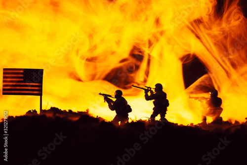 Fototapeta Battle scene with toy warriors near american flag with fire at background obraz