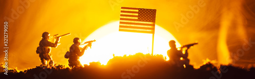 Fototapeta Battle scene with toy warriors near american flag in smoke with sunset at background, panoramic shot obraz