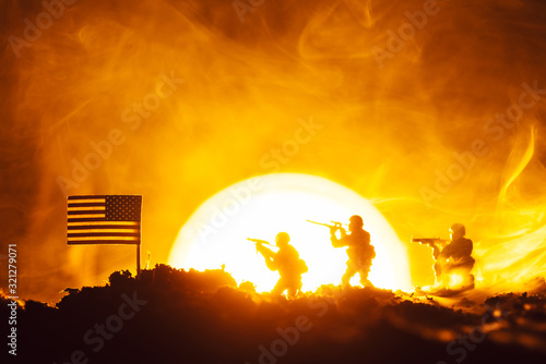 Fototapeta Battle scene of toy soldiers, american flag and fire with sunset at background obraz