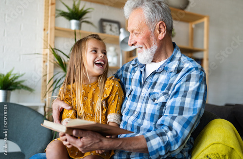 Cute grandfather and beautiful grandchildren reading a book - 321279203