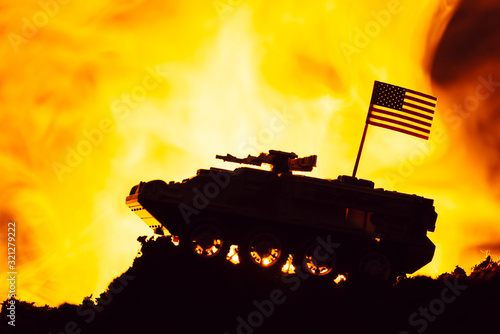 Fototapeta Battle scene with american flag on toy tank and fire at background obraz
