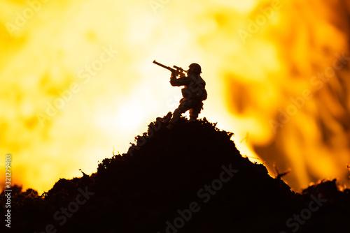 Fototapeta Battle scene with toy warrior on battleground and fire at background obraz