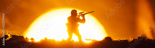 Fototapeta Battle scene with toy soldier, smoke and sunset at background, panoramic shot obraz