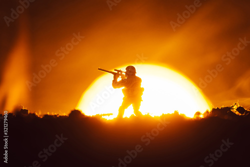 Fototapeta Toy soldier with smoke and sunset at background, battle scene obraz