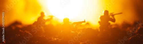 Fototapeta Battle scene of toy soldiers with sun on orange background, panoramic shot obraz