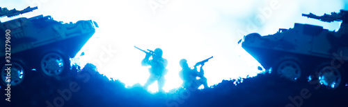 Fototapeta Battle scene with toy warriors and tanks with lighting on blue background, panoramic shot obraz